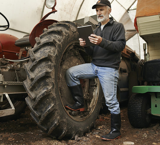 Farmer with a tractor looking at a tablet