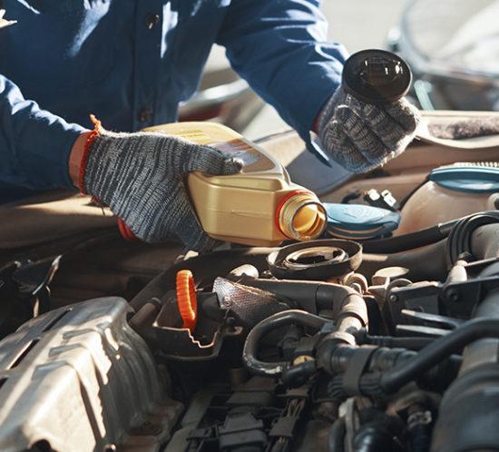 Mechanic putting oil in a car
